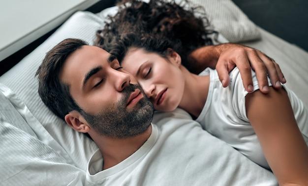 自宅のベッドで一緒に寝ている間抱き締める美しい若いカップル