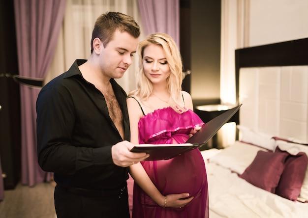 아름 다운 젊은 부부 남편과 아내는 미래의 아기를 위해 침대를 선택하는 가구 카탈로그를보고.