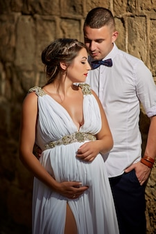 Beautiful young couple, husband and pregnant wife in a white lace dress in each other's arms