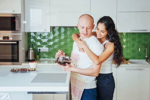 Beautiful young couple i talking, looking  and smiling while cooking in kitchen.