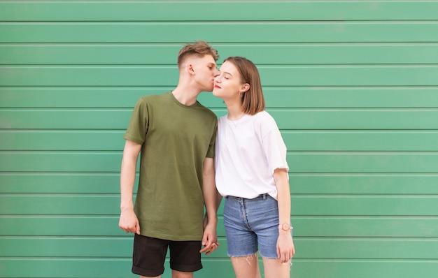 Красивая молодая пара в стильном повседневном платье, стоя на зеленом