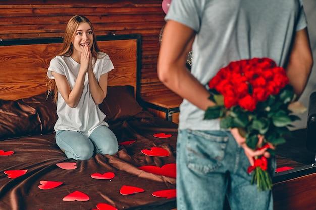 침실에서 아름 다운 젊은 부부 남자는 그의 뒤의 뒤에 빨간 장미 꽃다발을 숨 깁니다.
