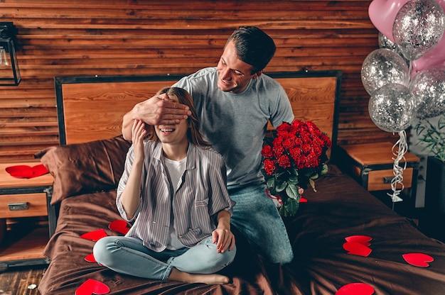 침실에서 아름 다운 젊은 부부. 빨간 장미를 가진 남자가 여자의 눈에 손을 감아 놀라게한다.