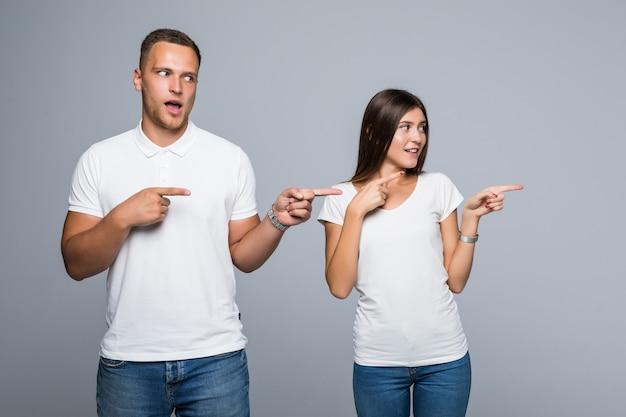 밝은 회색 배경에 고립 된 캐주얼 의류에 아름 다운 젊은 부부는 뭔가에 보여주는 흰색 티셔츠를 입고