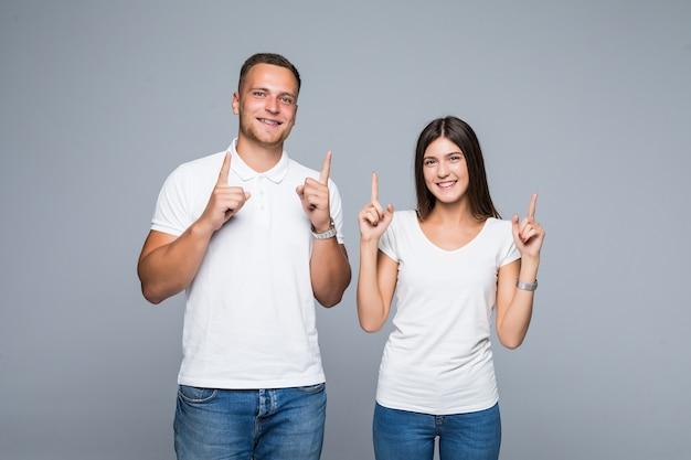 カジュアルな服装の白いtシャツとジーンズで指を持ち上げて美しい若いカップル