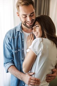 家で恋をしている美しい若いカップル、窓際に立って、抱きしめる