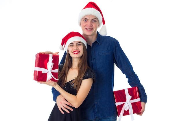 愛の美しい若いカップルは白い壁に分離されたクリスマスを祝う