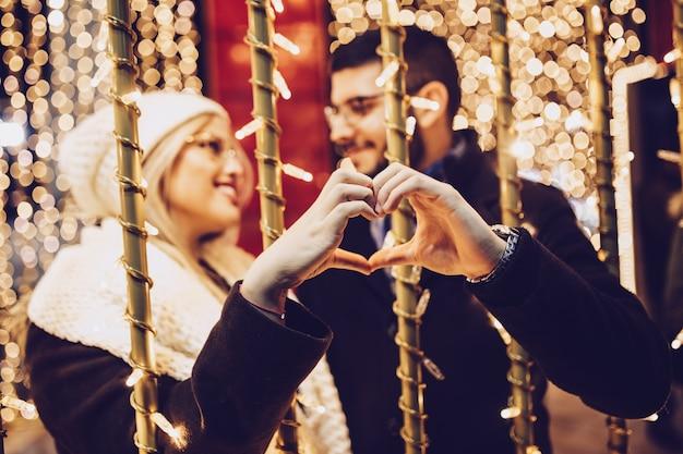 街の通りでクリスマスや新年の夜を楽しんで恋に美しい若いカップル。