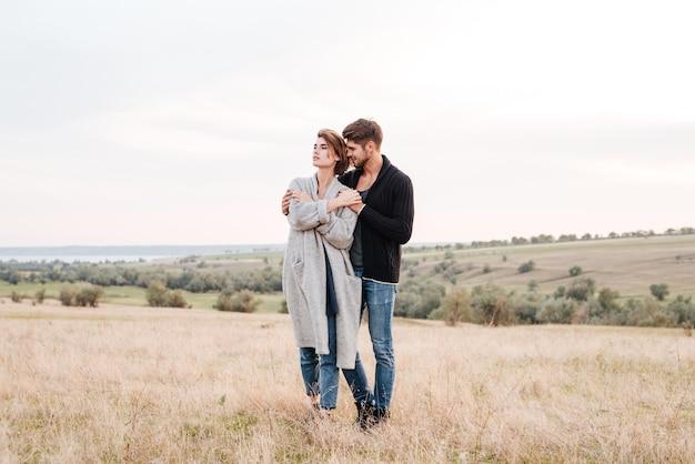 필드에 서 있는 동안 포옹 사랑에 아름 다운 젊은 부부