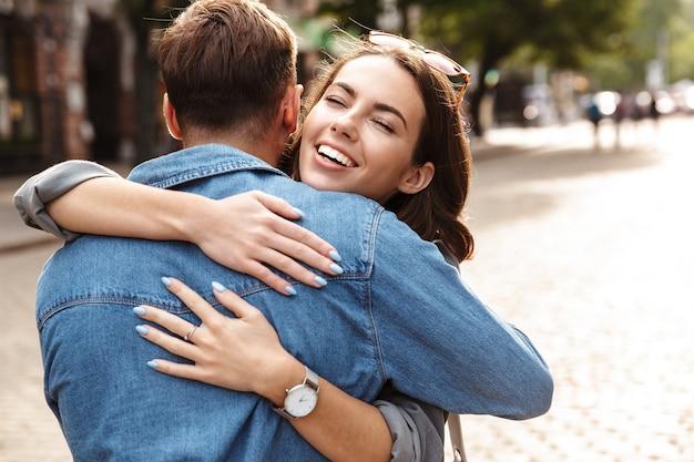 街の通りで、抱き締めて、屋外で恋をしている美しい若いカップル