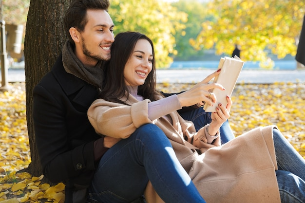Красивая молодая влюбленная пара проводит время вместе в парке осенью, читая книгу, сидя под деревом