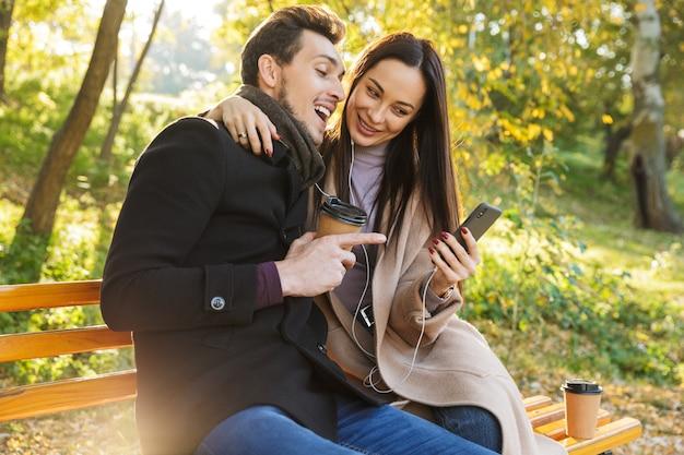 秋の公園で一緒に時間を過ごし、ベンチに座って、イヤホンで音楽を聴くのが大好きな美しい若いカップル