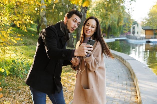 秋の公園で一緒に時間を過ごしたり、歩いたり、イヤホンで音楽を聴いたりするのが大好きな美しい若いカップル
