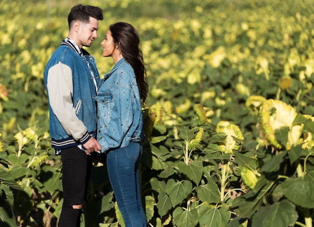 ヒマワリのフィールドに立っている愛の美しい若いカップル。