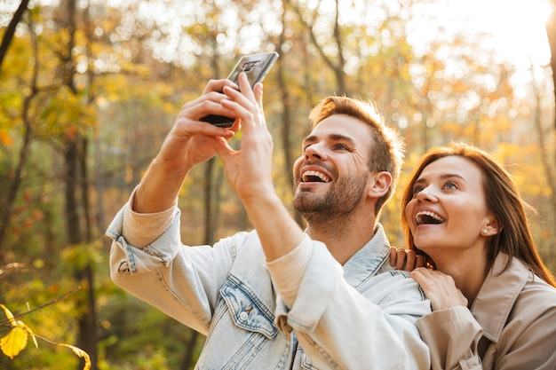 秋の公園で時間を過ごしながら、自分撮りをしながら携帯電話を使用して恋をしている美しい若いカップル
