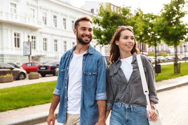 街の通りを屋外で歩いて、抱き締めて恋をしている美しい若いカップル