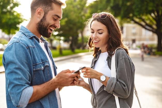 Красивая молодая влюбленная пара гуляет на улице по городской улице, используя мобильные телефоны