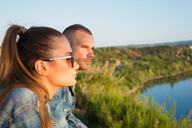 川を見て、景色を楽しむ関係の美しい若いカップル