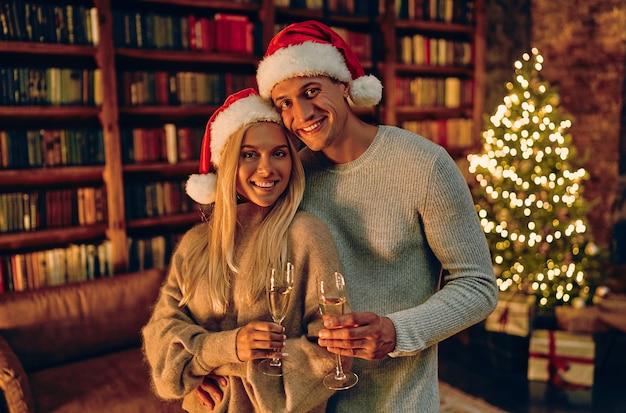 Красивая молодая пара в шляпах санты держит бокалы шампанского и улыбается во время празднования нового года дома.
