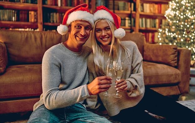 산타 모자에있는 아름 다운 젊은 부부는 샴페인 잔을 들고 집에서 새 해를 축 하하는 동안 웃 고.