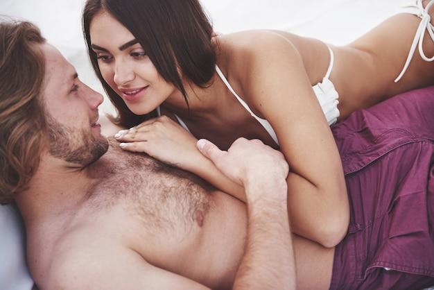Красивая молодая пара в купальниках на пляже против песка, улыбка и объятия.