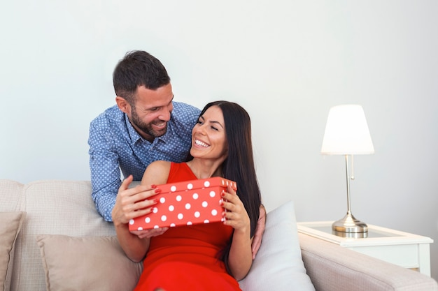 Beautiful young couple is celebrating at home. handsome man is giving his girlfriend a gift box.
