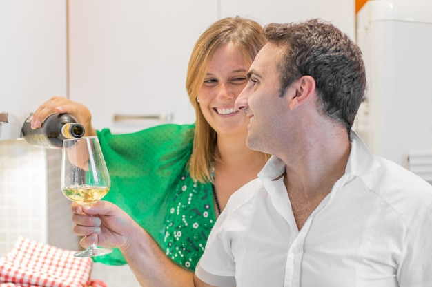 아름 다운 젊은 부부는 와인을 마시고 집에서 부엌에서 웃