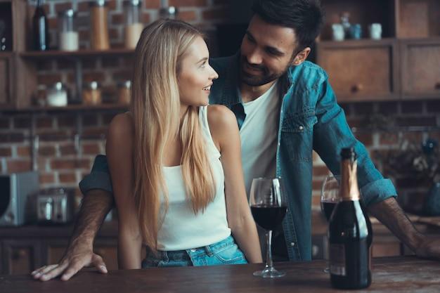 美しい若いカップルは、自宅のキッチンで料理をしながらワインを飲み、笑顔です。
