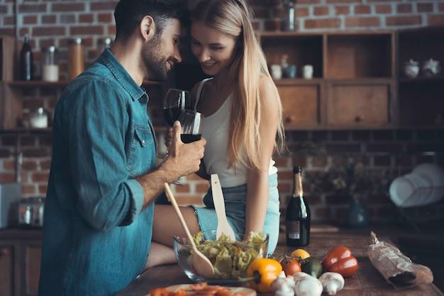아름 다운 젊은 부부는 와인을 마시고 집에서 부엌에서 요리하는 동안 웃 고.