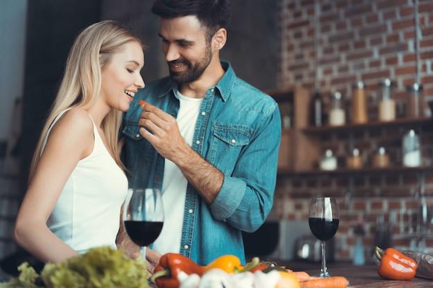 Красивая молодая пара кормит друг друга и улыбаются, готовя на кухне дома.
