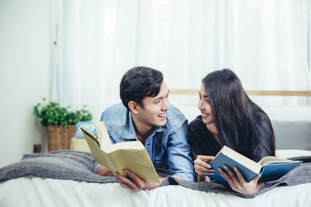 Beautiful young couple is feeding smiling while reading a book in bedroom