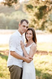 美しい若いカップルが公園で抱いています。