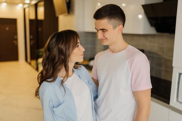 美しい若いカップルはお互いを見て、自宅のキッチンで一緒に時間を過ごしながら笑顔です。愛するカップルのコンセプトです。