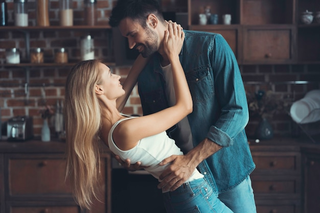 Beautiful young couple is looking at each other and smiling while dancing in kitchen.