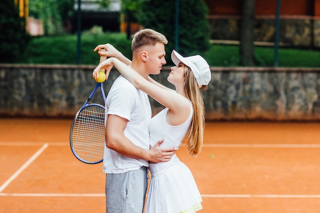 아름다운 젊은 부부가 화창한 날씨에 야외에서 테니스를 치고 있다