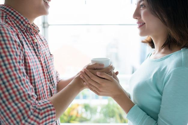 Красивая молодая пара улыбается, пьет чай на кухне дома