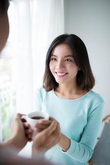 美しい若いカップルが自宅のキッチンでお茶を飲みながら笑っている