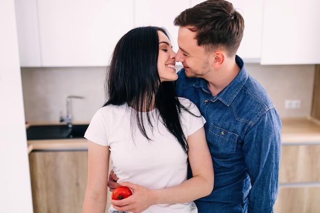 A beautiful young couple is talking and smiling and kissing while preparing healthy food