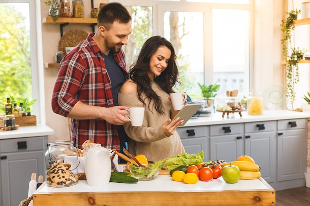 Beautiful young couple is talking,  smiling while eating tea or coffee and drinking in kitchen at home.