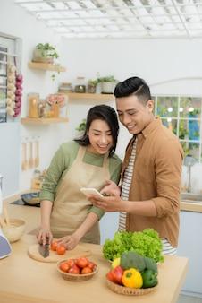 아름다운 젊은 부부는 집에서 부엌에서 요리하는 동안 휴대폰을 사용하고 웃고 있다