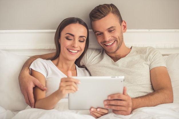 Beautiful young couple is using a digital tablet