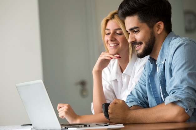 Beautiful young couple is using a laptop and smiling while drinking coffee