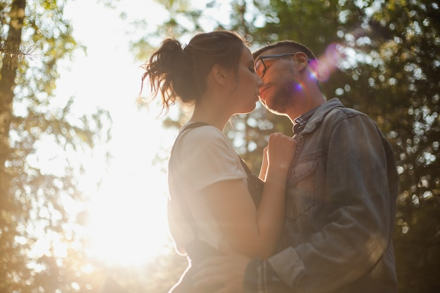 A beautiful young couple kiss in the forest