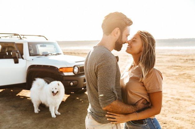Beautiful young couple in love embracing while standing at the beach, vacation trip