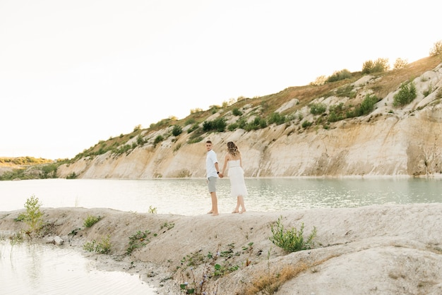 A beautiful young couple in love, a man and a woman embrace, kiss near a blue lake and sand at sunset.