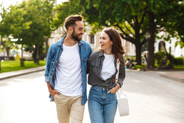 Beautiful young couple in love walking outdoors at the city street, hugging