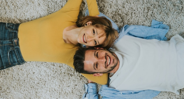 Beautiful young couple of lovers lying on the carpet at home smiling