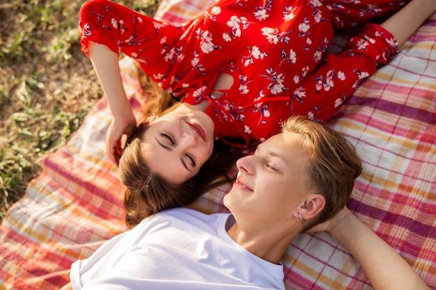 여름에 풀밭에 누워 있는 아름다운 젊은 부부