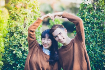 Beautiful young couple making heart shape with hands and Smiling happy in love outdoors