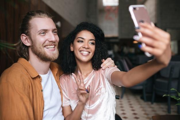 레스토랑에서 정면 핸드폰 카메라에 사진을 만드는 아름 다운 젊은 부부